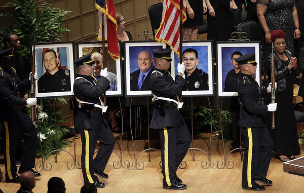 An honor guard passes photos of the fallen police officers during a memorial service at the Morton H. Meyerson Symphony Center, Tuesday, July 12, 2016, in Dallas. (Eric Gay/Associated Press)
