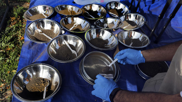 An environmental health specialist for the L.A. County Health Dept. places a soil sample collected from the front and back yard of a home on Ransom St. in Commerce, to be tested for possible lead contamination from the nearby and now closed Exide plant.