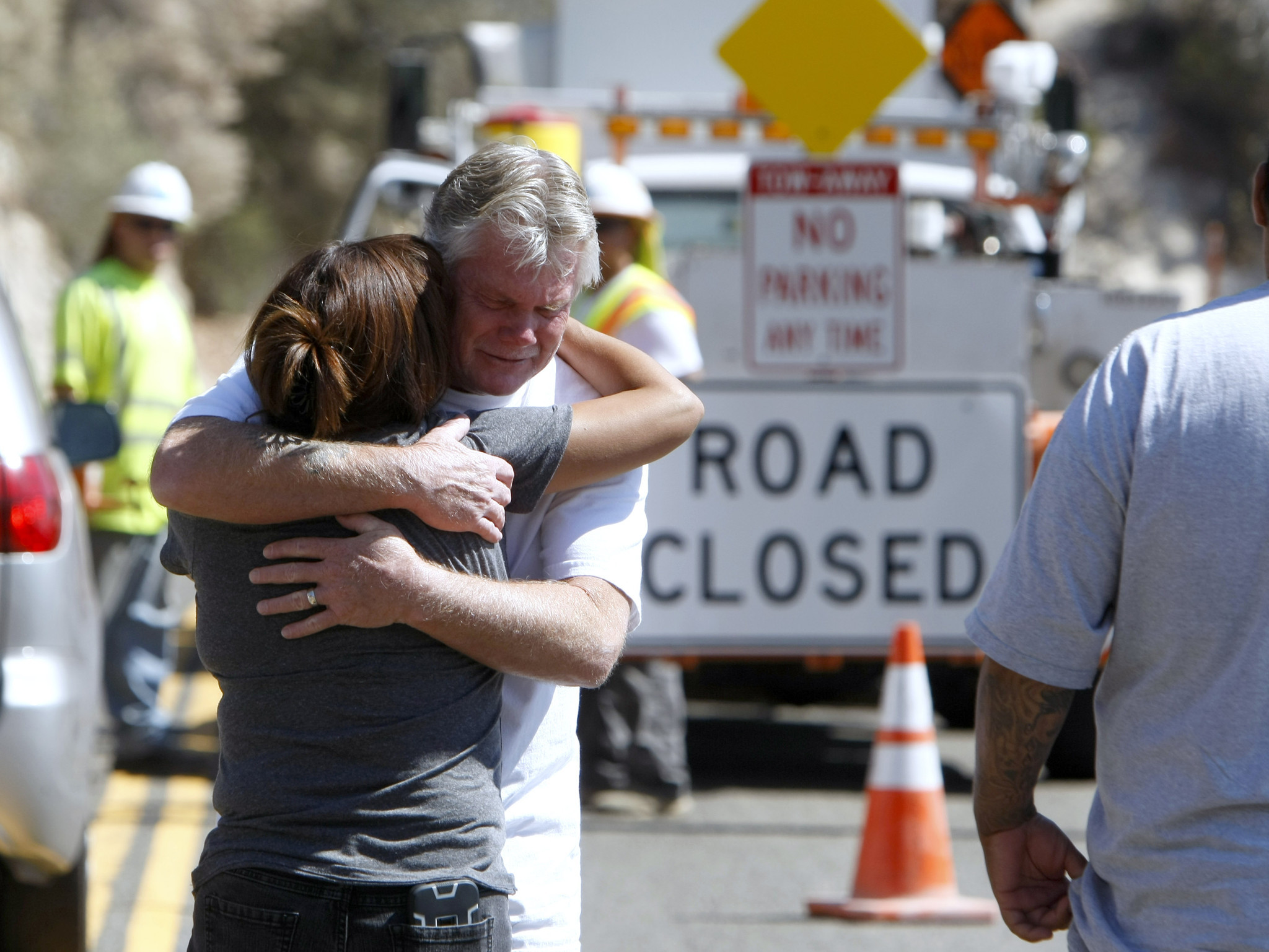 Mari Tovar, Samantha Ornelas' aunt, is hugged by the father of Kasey Vance, who did not want to give his name, as they arrive to find gates closing off Angeles Crest Highway near where the bodies of three people were being recovered Tuesday.