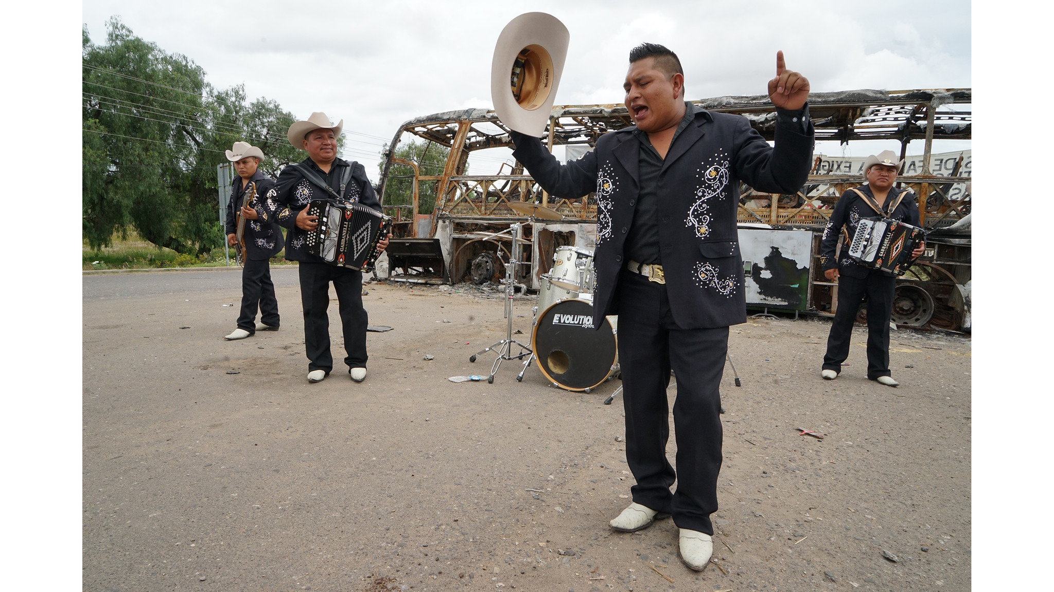Ramon Gonzales Hernandez, the lead singer of Grupo Accion Oaxaca , a norteo band,  performs in front of a burned-out bus at the entrance of Nochixtlan.