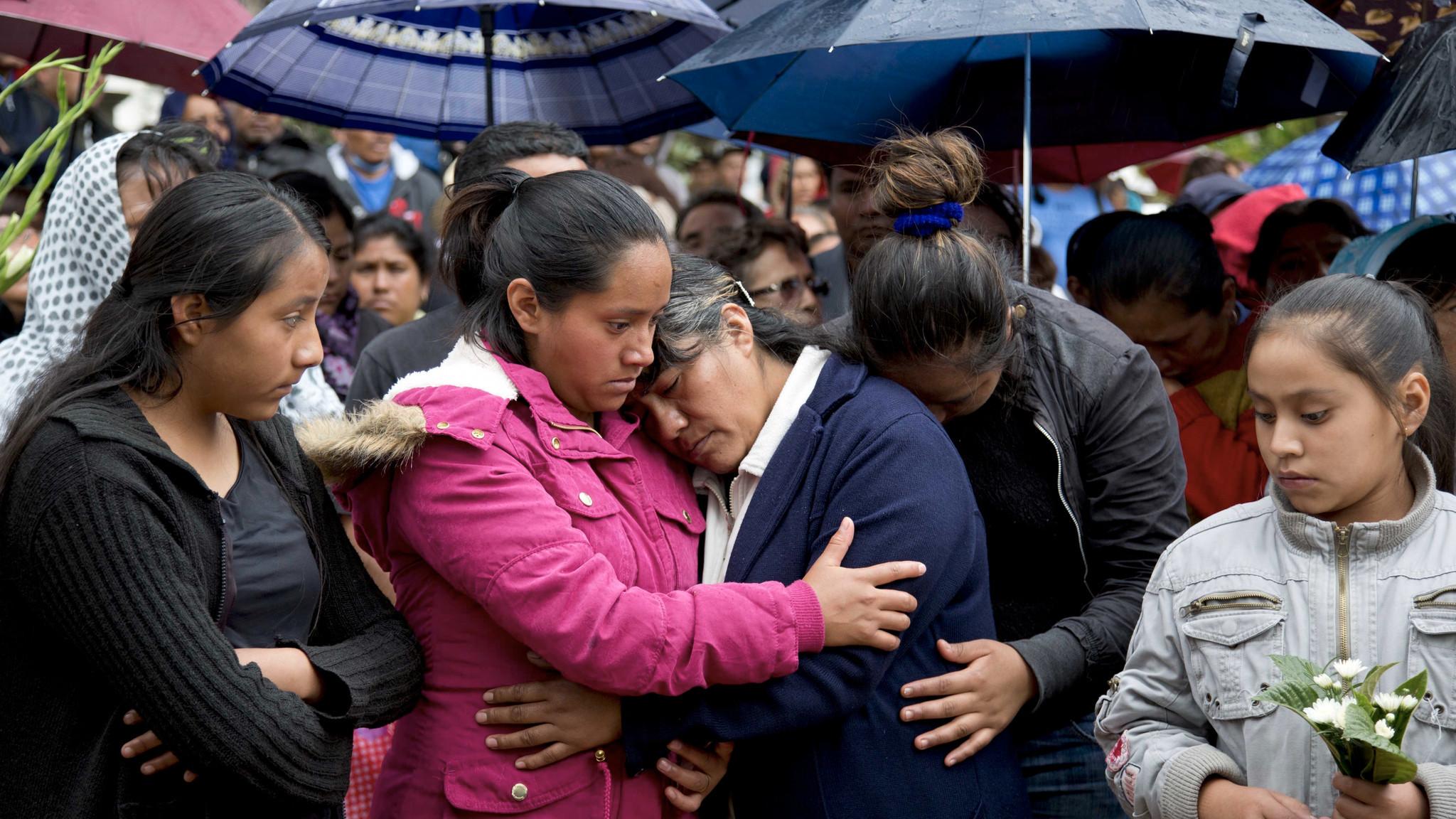 Patricia Sanchez Meza, mother of Jesus Cadena Sanchez is comforted by relatives at his funeral