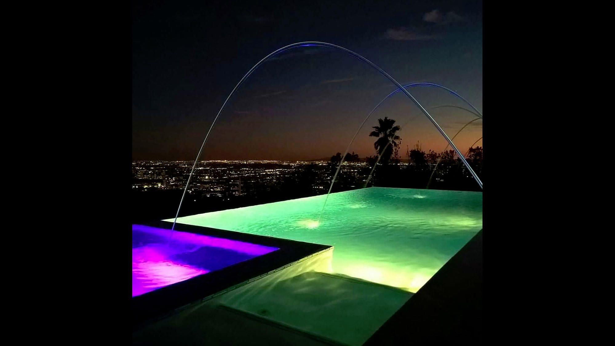 This infinity-edge pool by Poseidon Pools features lighted laminar deck jets, a swim jet system, color-changing lights, underwater speakers, an automatic pool cover and remote-control technology by OmniLogic.