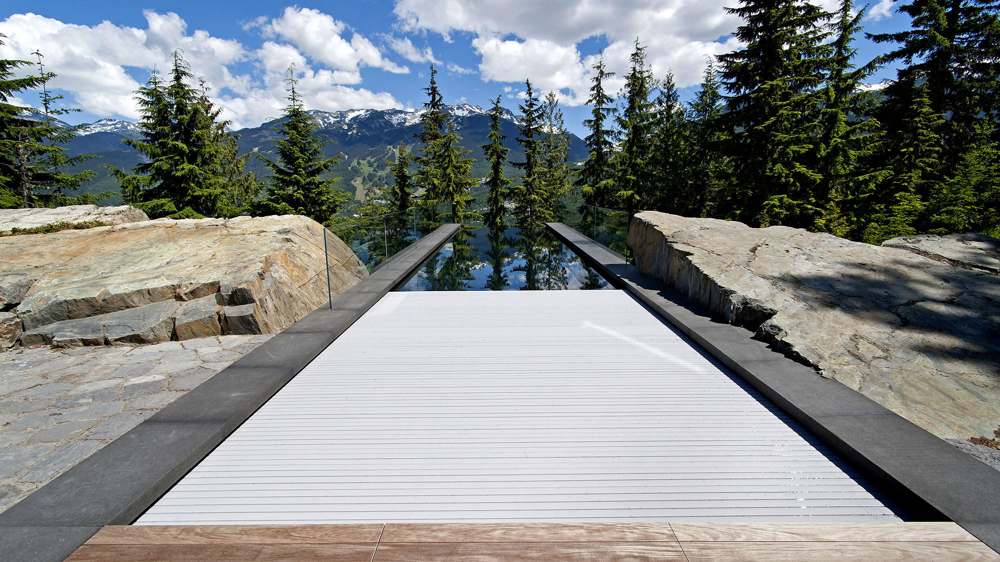 A cantilevered pool built by Alka Pool Construction over a hillside in Whistler, Canada, features an automated Hydralux cover from Aquamatic Cover Systems.