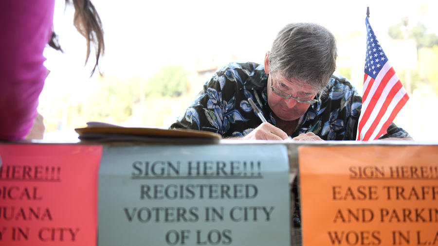 Tim Ecker collects signatures outside a grocery store in Silver Lake in August.