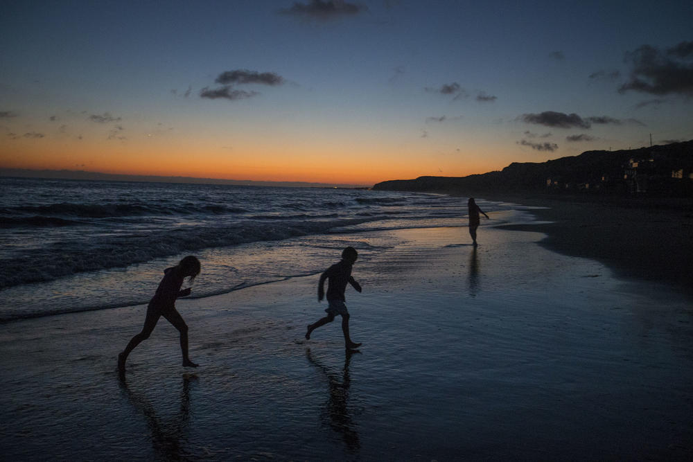 Children run along the beach at twilight near the Crystal Cove Beach Cottages. (Allen J. Schaben / Los Angeles Times)