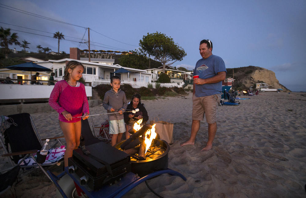 Isabella, 9, and Holden, 7, roast marshmallows over a beach fire with their parents, Steve and Amy Knuff, of Aliso Viejo at twilight at Crystal Cove Beach Cottages. (Allen J. Schaben / Los Angeles Times)