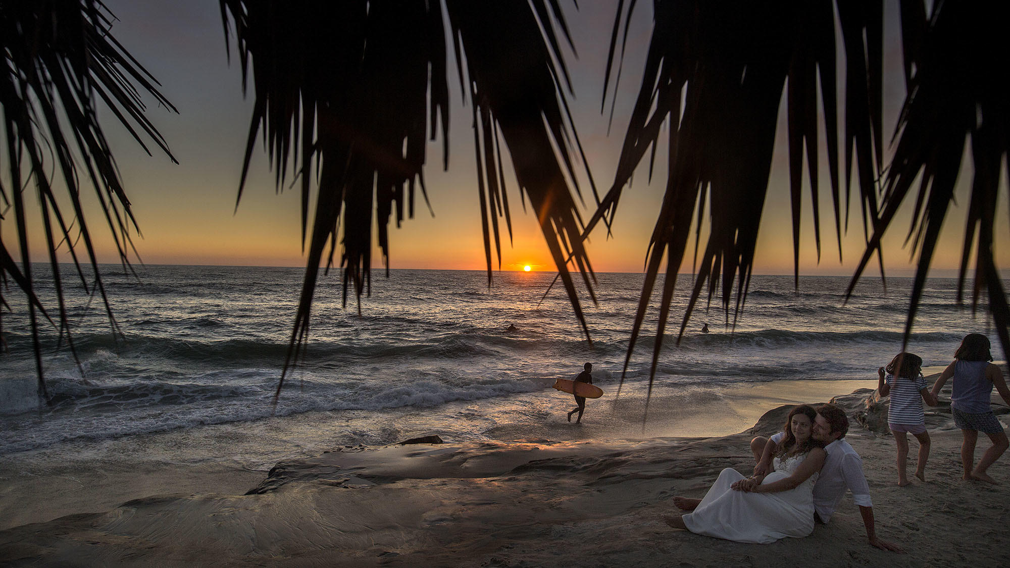 The palm fronds of a palapa reveal a surfer, a couple and children taking in a warm summer sunset at Windansea Beach in La Jolla. (Allen J. Schaben / Los Angeles Times)