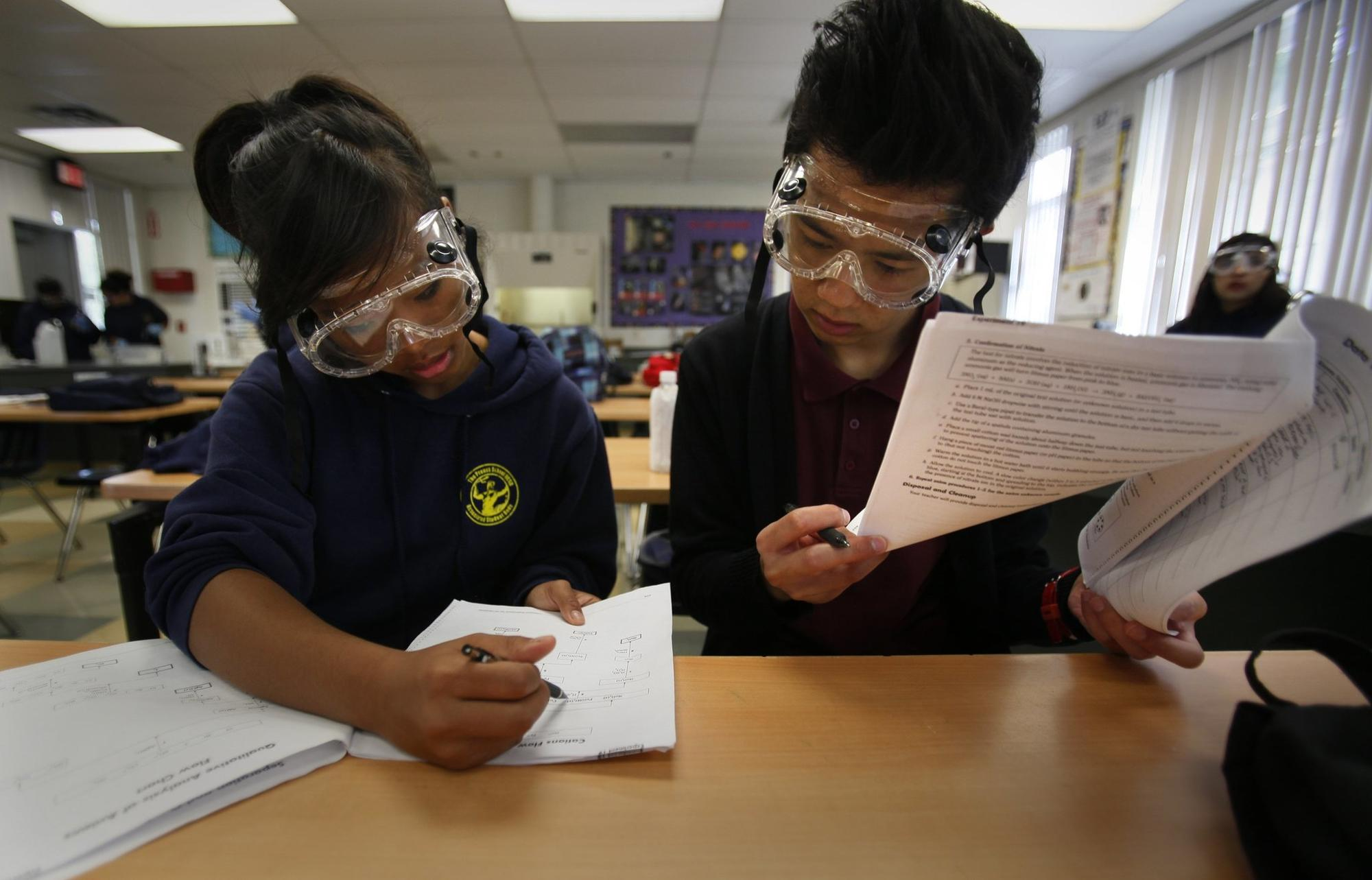 In an AP Chemistry class, Elayne Tram Nguyen, 18, left, and Destin Dao, 18, go over their notes for an experiment they were performing in class Tuesday morning. UCSD Preuss Sch