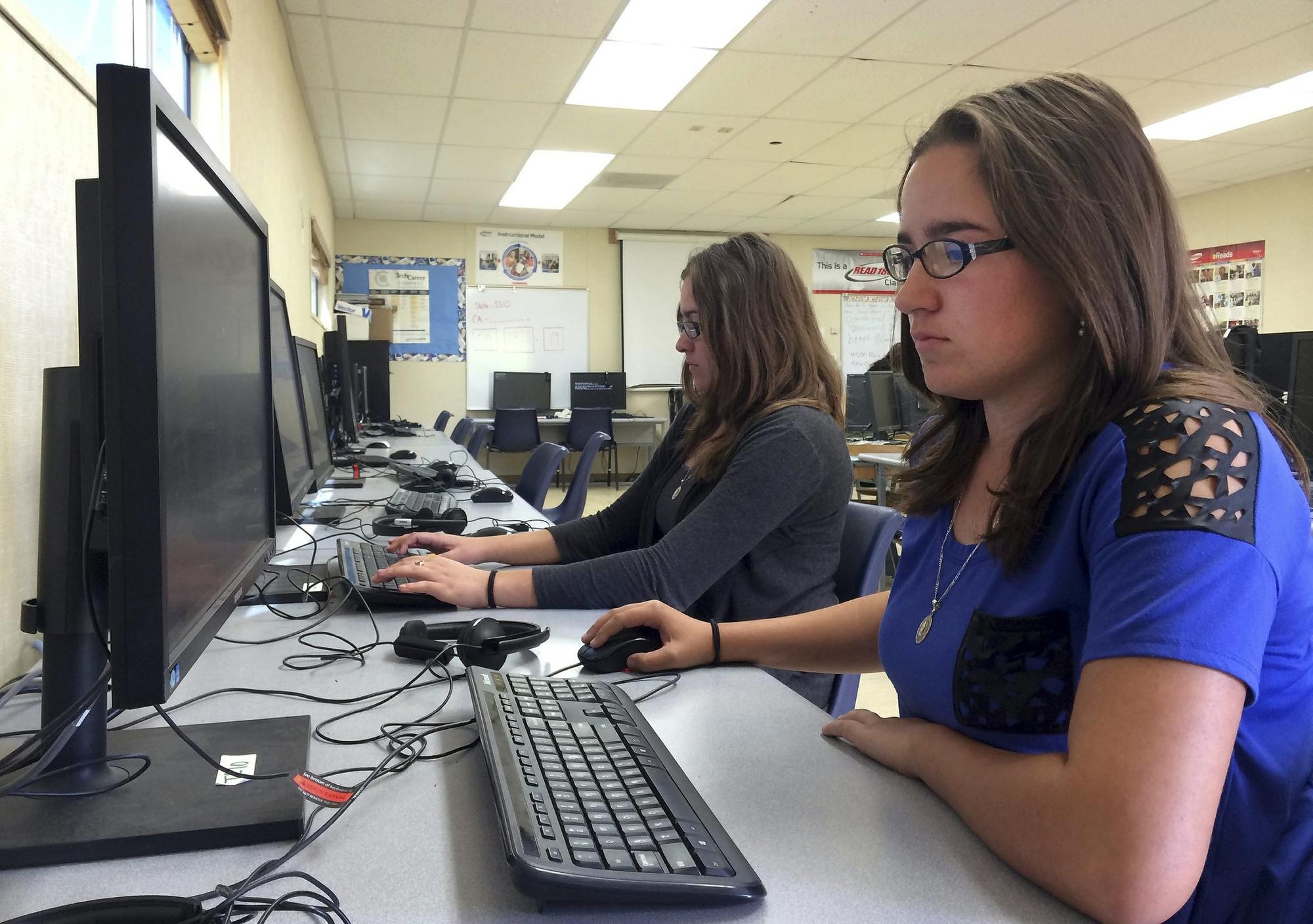 In this April 30, 2015 photo, Leticia Fonseca, 16, left, and her twin sister, Sylvia Fonseca, right, work in the computer lab at Cuyama Valley High School after taking the new Co