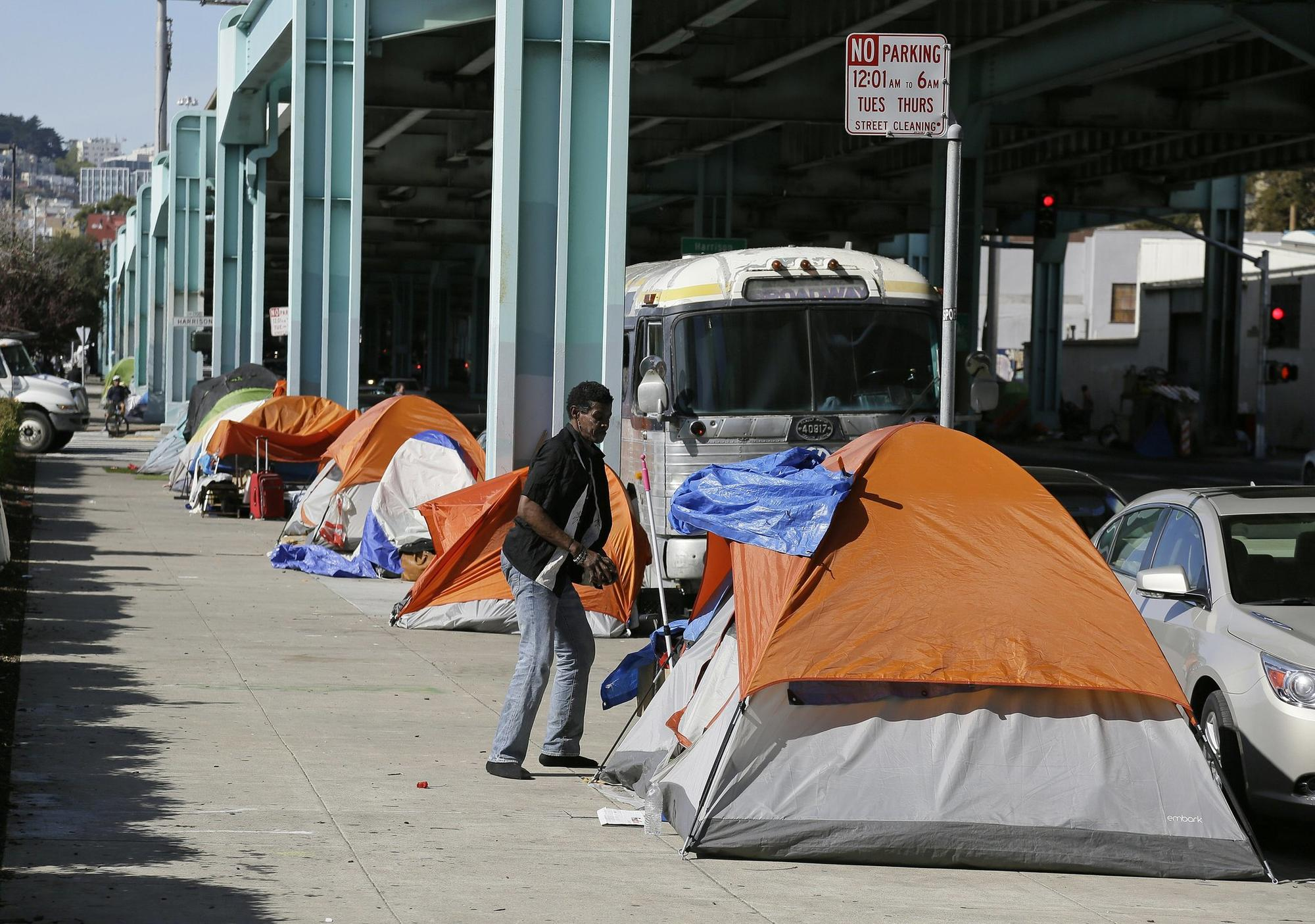 A man stand outside his tent on Division Street Tuesday, Feb. 23, 2016, in San Francisco. San Francisco health officials declared a tent city that has been growing along a city s