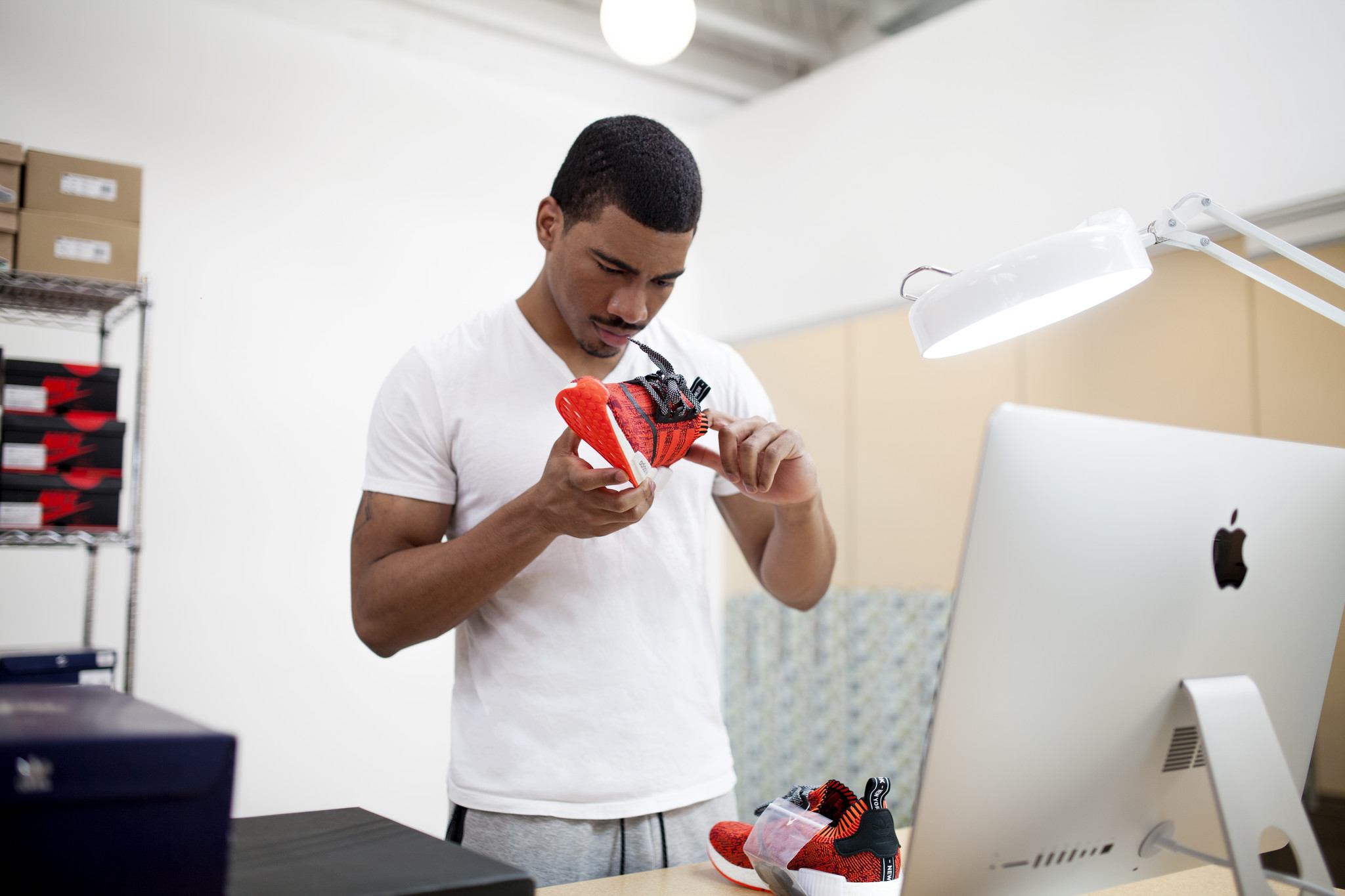 "A GOAT authentication specialist studies a pair of Adidas NMD ""Red Apple,"" a pair of shoes of which only 200 exist."