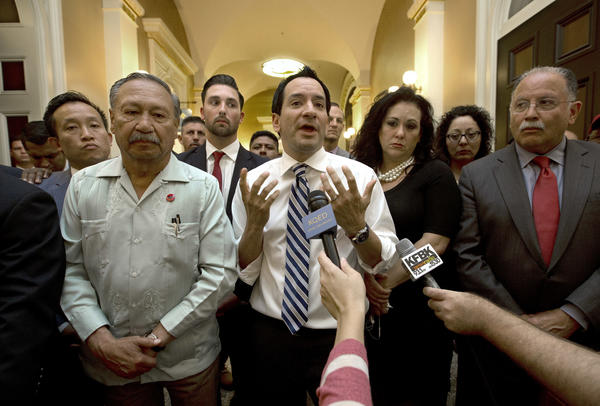 Assembly Speaker Anthony Rendon (D-Paramount) last month speaks in support of the legislation expanding overtime pay for farmworkers. He is flanked by Arturo Rodriguez, president of the United Farm Workers, on the left, and by Assemblywoman Lorena Gonzalez (D-San Diego), the author of the legislation, on the right. (Rich Pedroncelli / Associated Press)