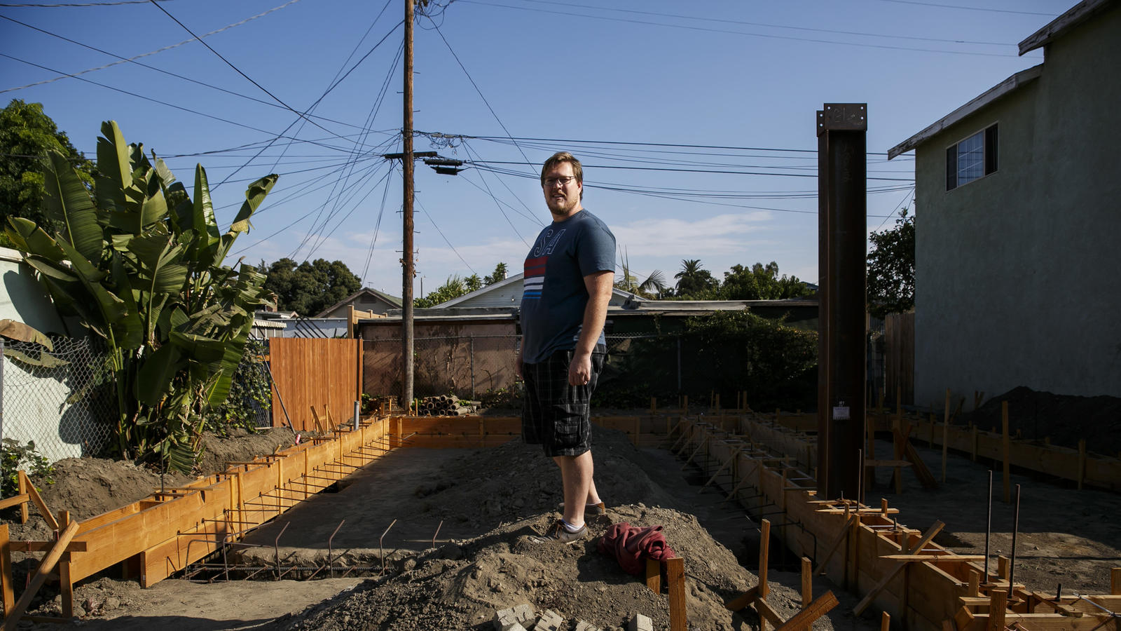 John Gregorchuk stands amid construction of a secondary dwelling unit that has been stalled in his backyard in Los Angeles. (Marcus Yam / Los Angeles Times)