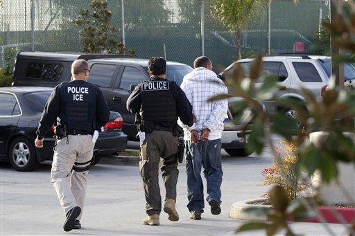 In this March 30, 2012 photo, Immigration and Customs Enforcement (ICE) agents take a suspect into custody as part of a nationwide immigration sweep in Chula Vista, Calif. Federa