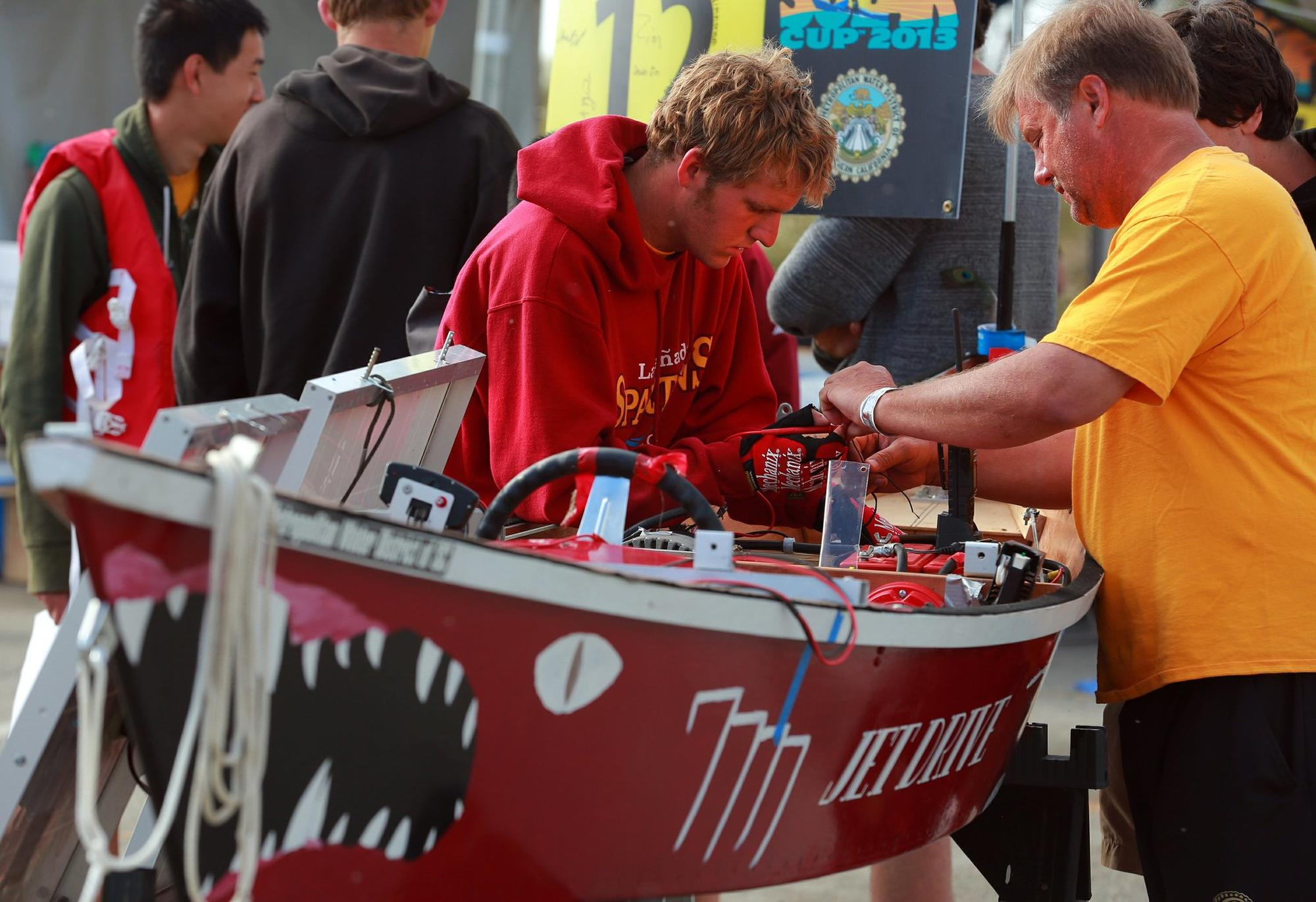 Shane Bell, left, a junior at La Canada High School, works with team member Steve Zimmerman on the finishing touches of the jet drive engine, the only one in Sunday's competiti