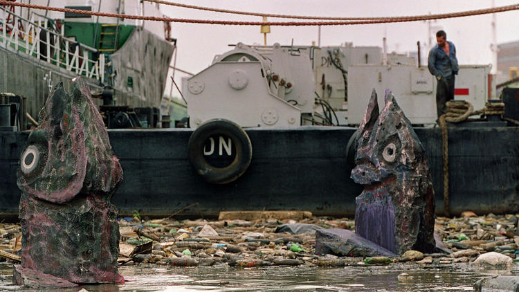 Giant fish sculptures float through garbage in the Riachuelo River as part of a Greenpeace campaign to raise awareness about pollution in the Buenos Aires waterway in 2000.