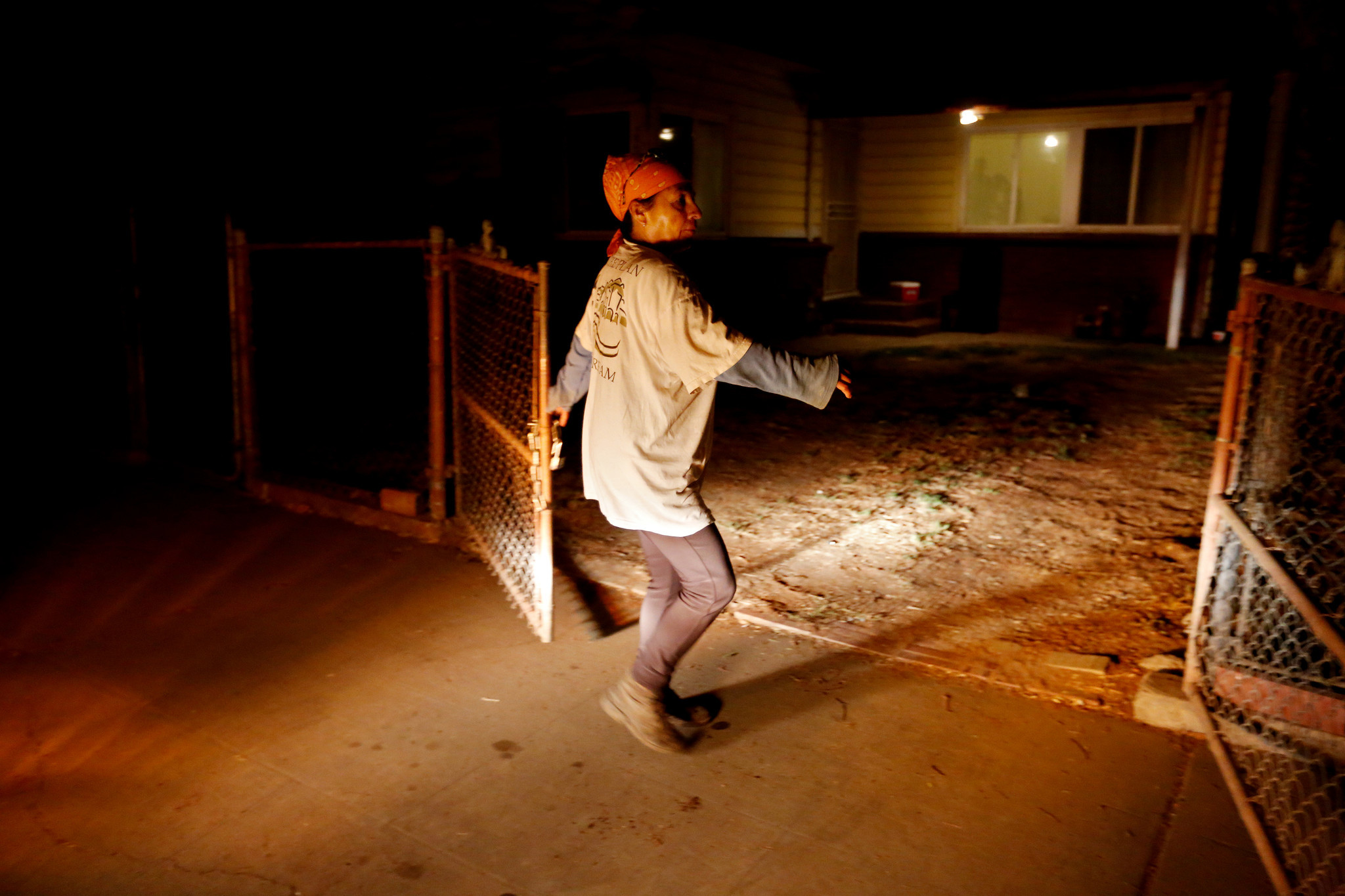 Lourdes Cardenas, 53, locks the gate to her home before driving to a gas station to meet other farmworkers to pick grapes in Fresno.