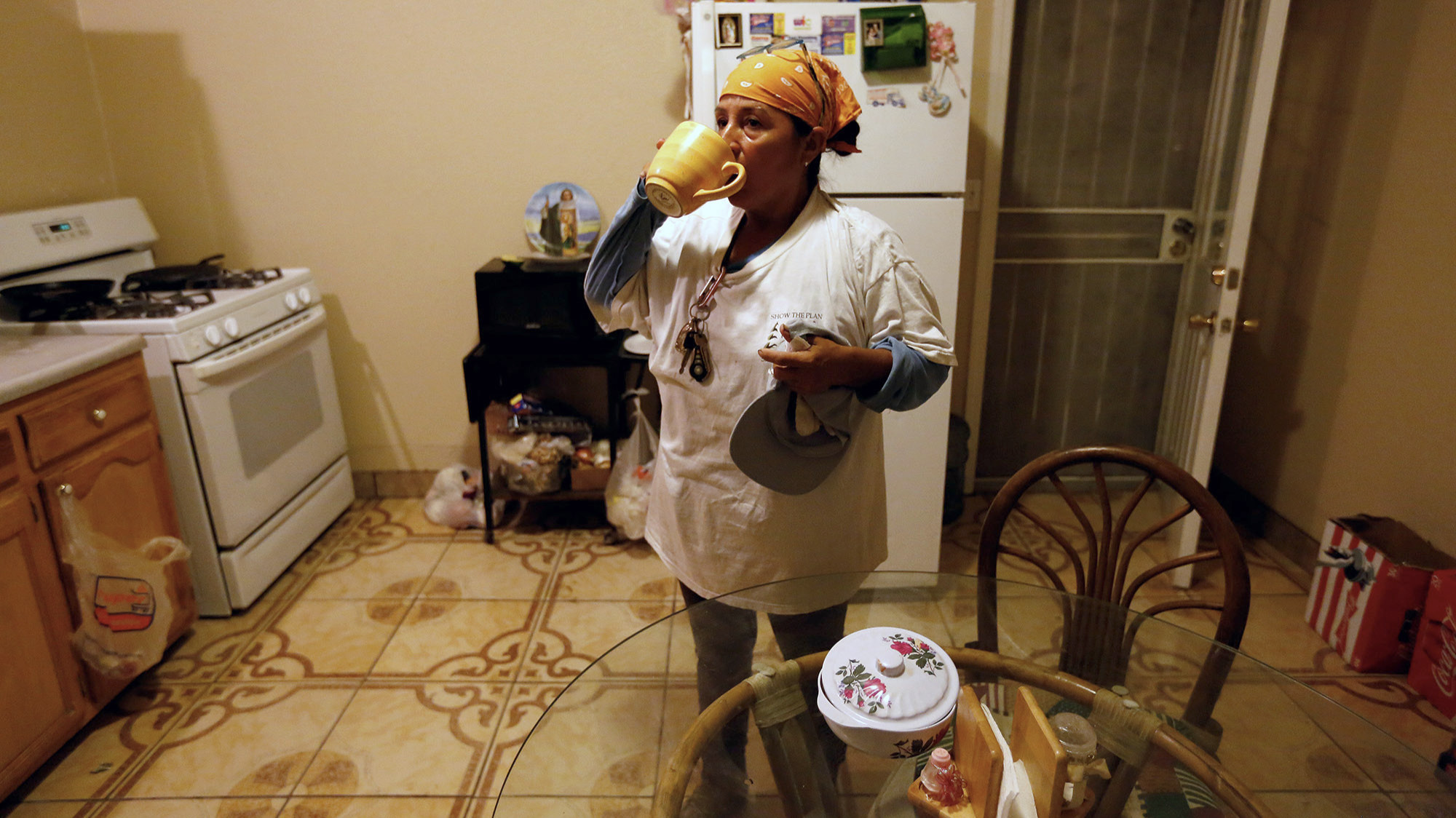 Lourdes Cardenas, 53, after preparing lunch has a cup of coffee before leaving a two-bedroom house she rents with her husband, nephew and five roommates, to pick grapes in Fresno.