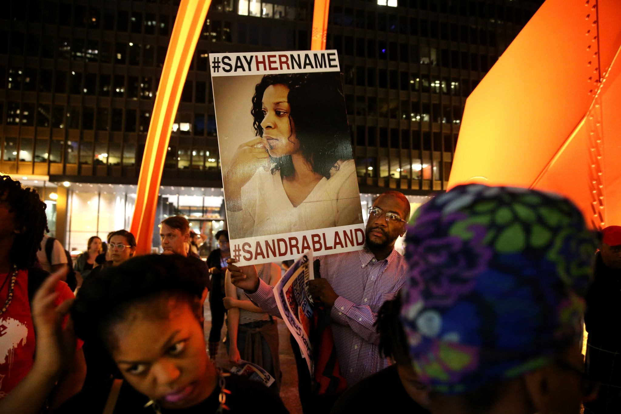 Tokunbo Adenekan of Baltimore holds a sign during a candlelight vigil in Chicago in July to mark the one-year anniversary of Sandra Bland's death.