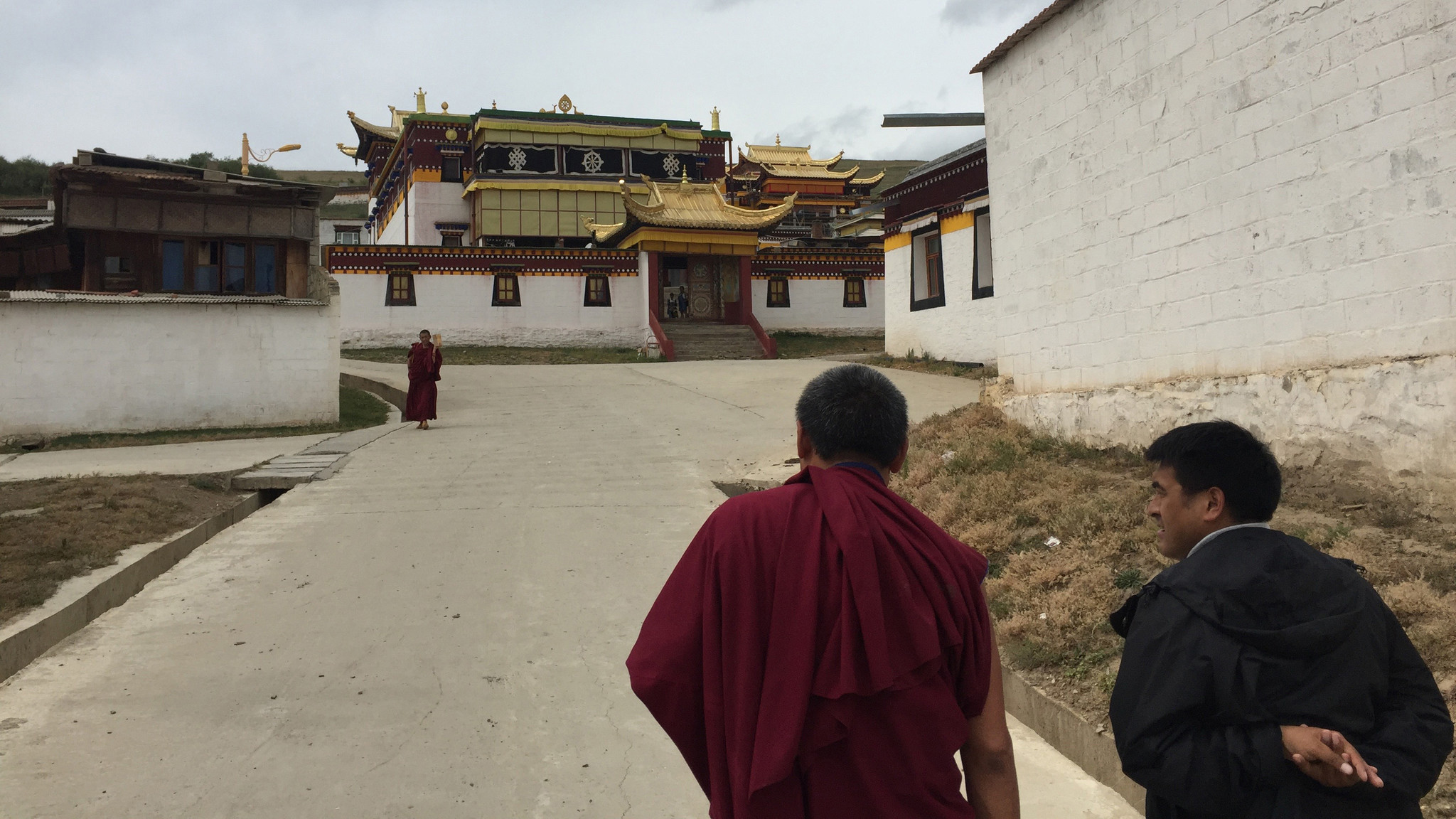 A monk and an official at the Dazha Monastery in Ruoergai County, Aba prefecture, chat as they walk toward a prayer room.