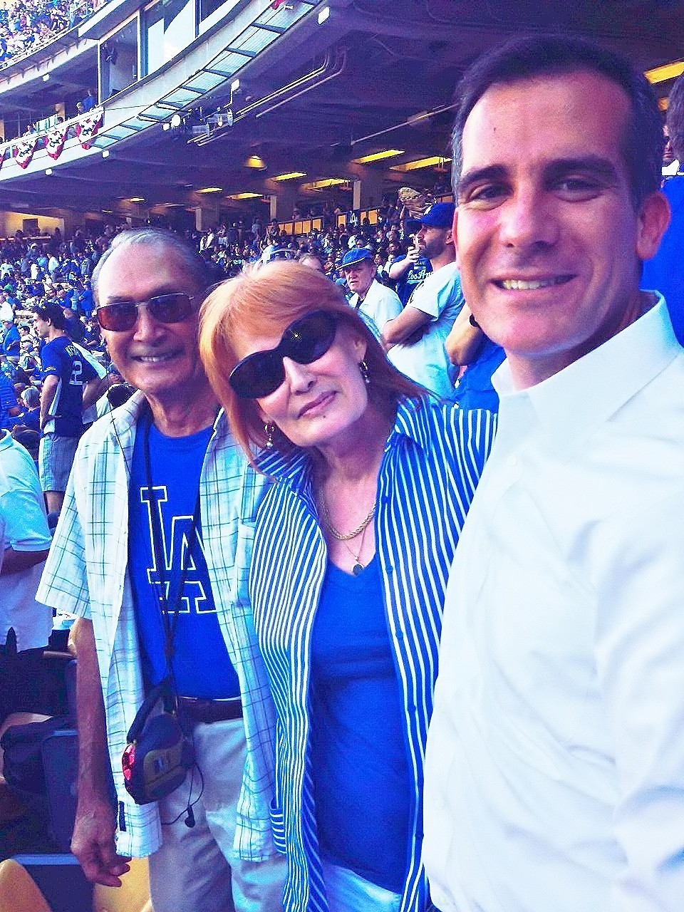 Suzanne Lewis poses with her father, Louis Avila, and L.A. Mayor Eric Garcetti at a Dodgers game in 2015.