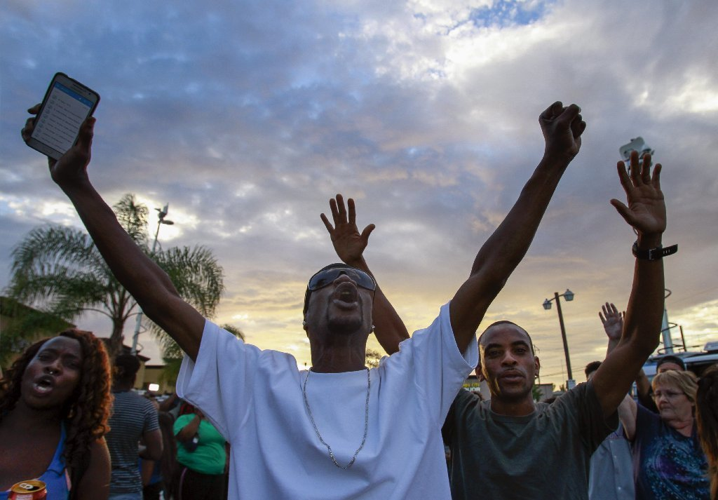 People yell toward police at the scene where a black man was shot by police earlier in El Cajon, east of San Diego, Calif., Tuesday, Sept. 27, 2016.
