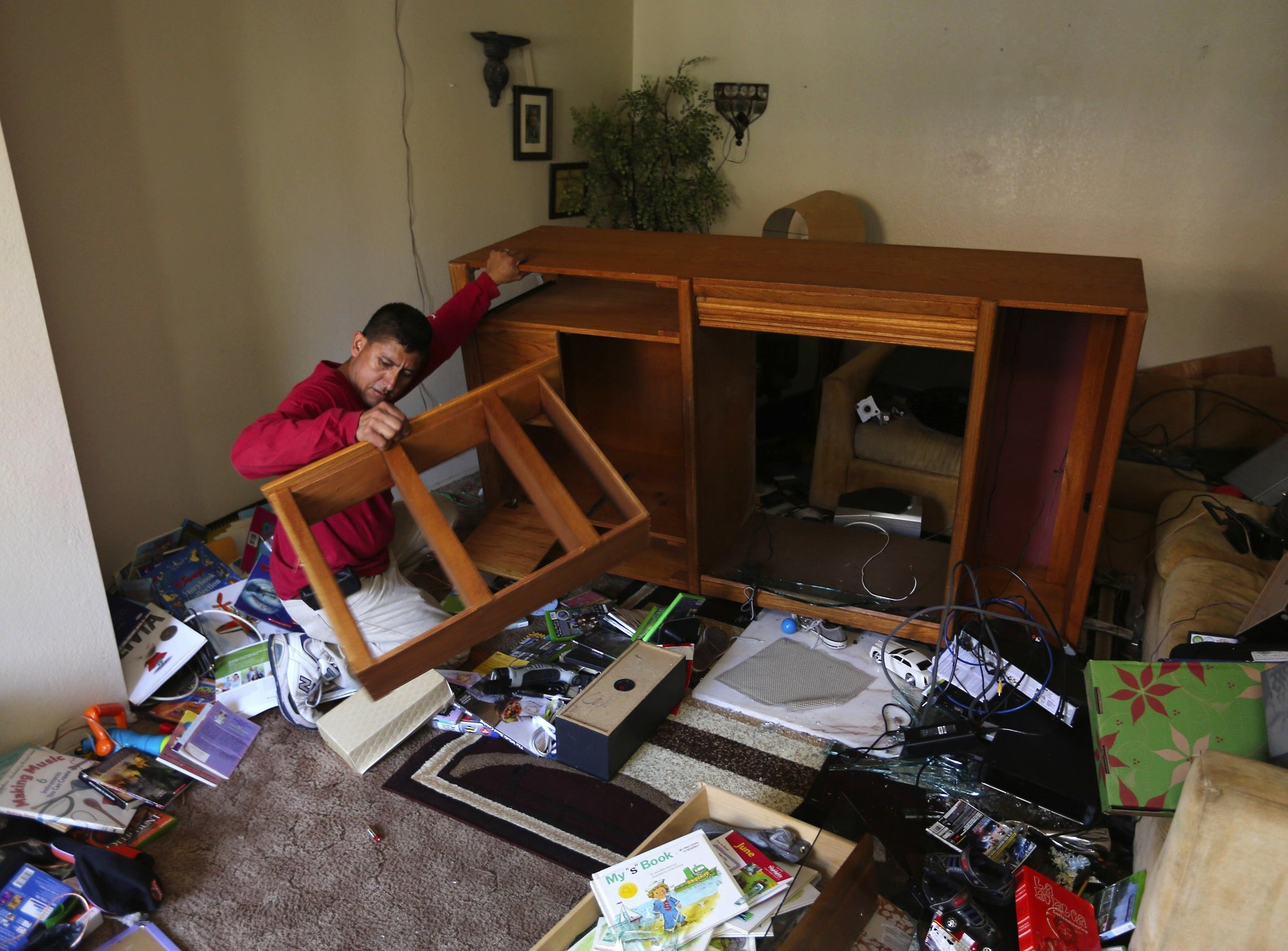 Jamie Gudino cleans up the damage from an early morning earthquake in Napa, Calif., on Aug. 24, 2014,