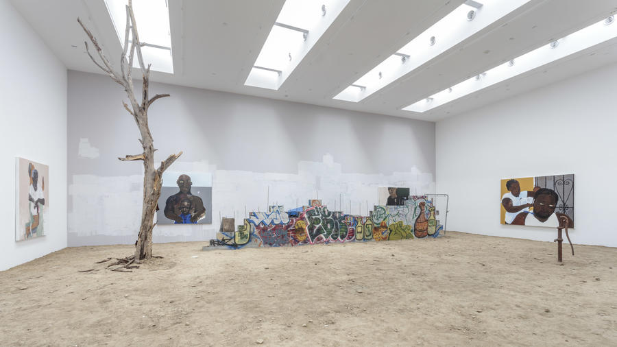 Henry Taylor paintings installed in a stage set of an urban vacant lot.