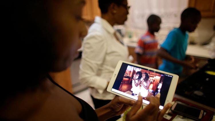 Trisha Michael scrolls through photos on an electronic tablet showing her twin sister, Kisha.