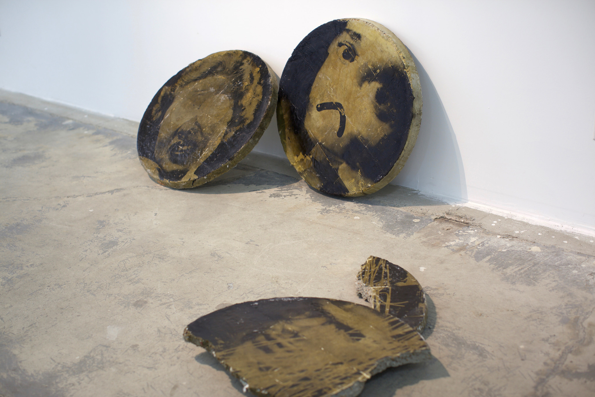 """Zachary Roach's """"Tablet 1,"""" """"Tablet 2"""" and """"Tablet 3,"""" 2016, concrete, photo emulsion, each 26 inches in diameter."""