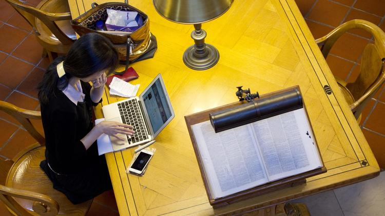 A woman works on her laptop in the Rose Main Reading Room of the New York Public Library. (Mark Lennihan / Associated Press)