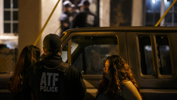 ATF agents speak to a suspect detained in handcuffs, during a house raid in the San Fernando Valley on Nov. 2, 2016.