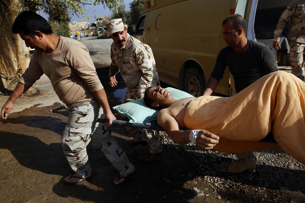 Wounded soldiers and civilians are carried into a field hospital.