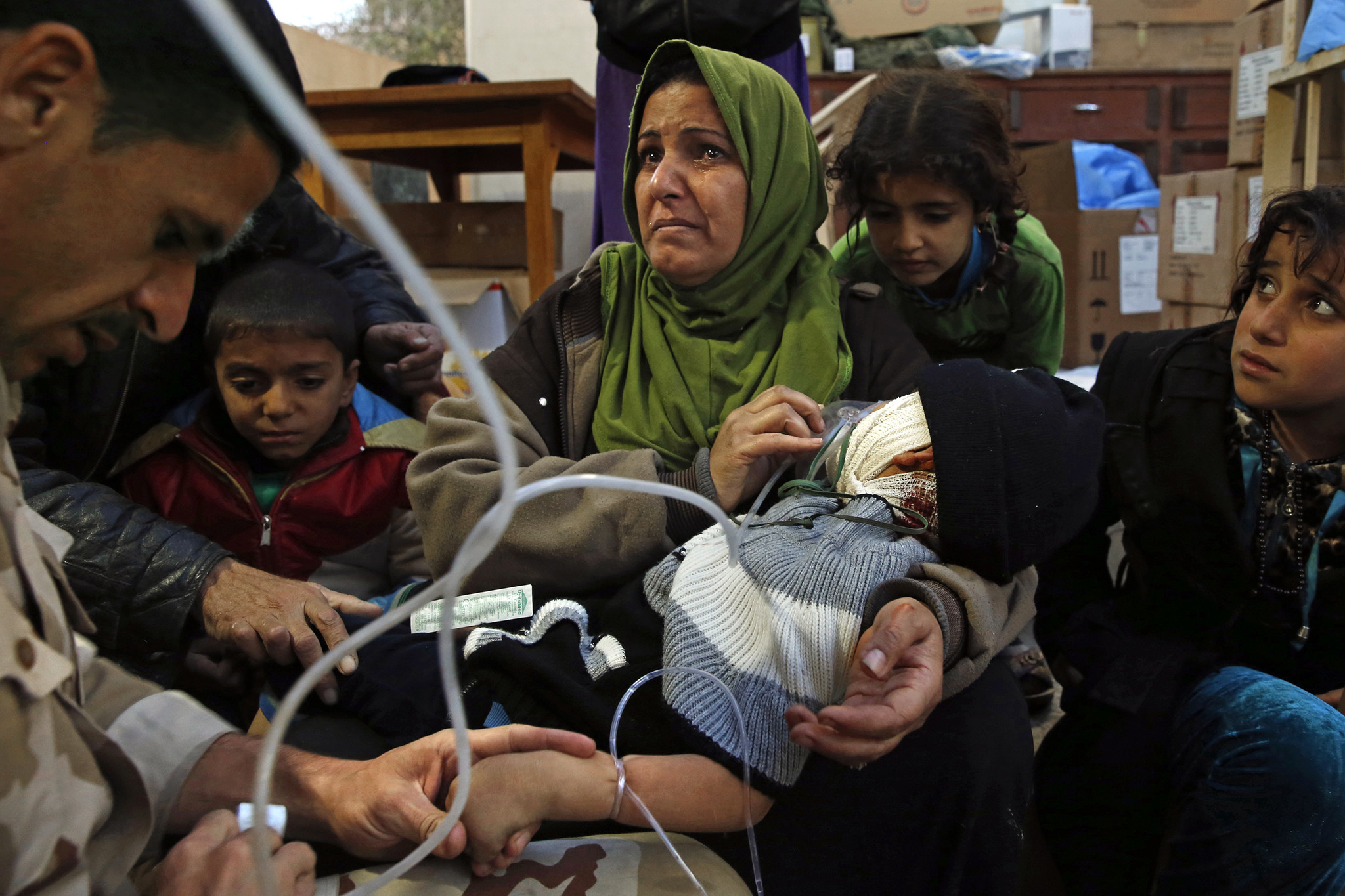 Wafa Abdel Raza, 39, holds her son Mahmoud Setar, 4, as the doctors give him oxygen and and fluids. The boy's head was badly injured when a truck bomb exploded near their home.
