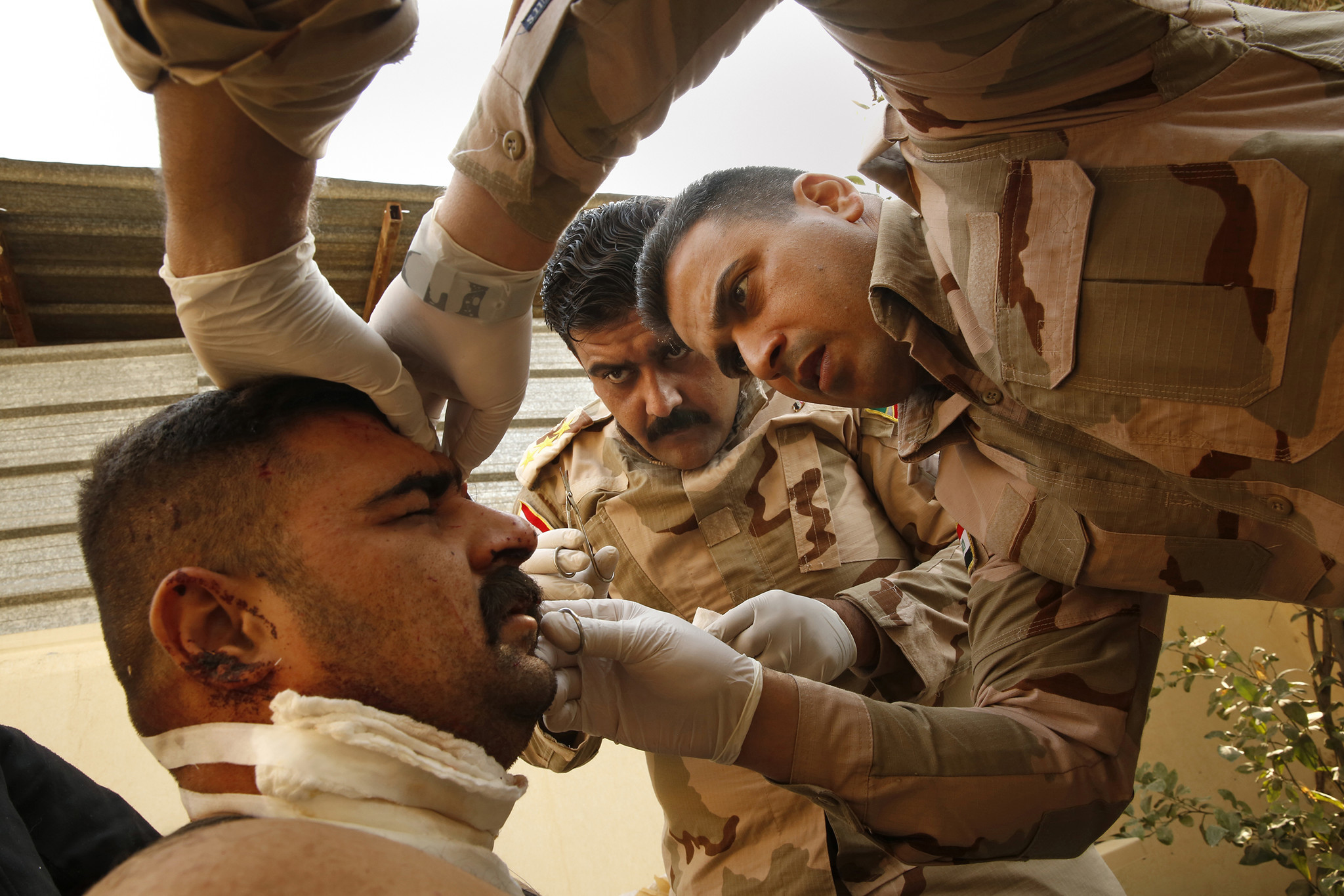 Capt. Osama Fuad Rauf, 33, center, and Maj. Mohammed Hassan Abdullah, left, 35, treat a soldier who was wounded in the fight against Islamic State near Mosul.