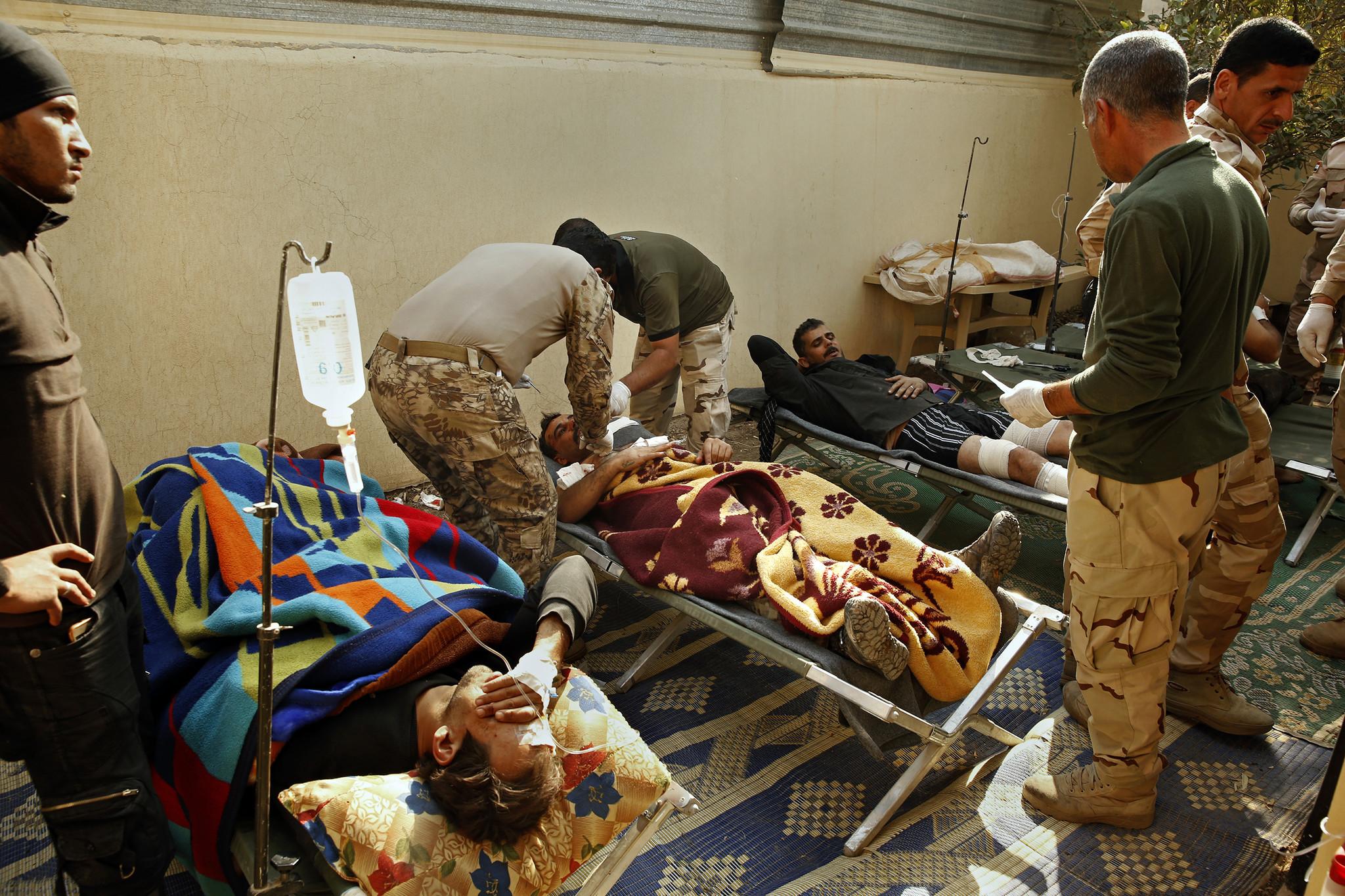 Maj. Gen. Raad Mohssan Dakhel treats a soldier hit by shrapnel from a car bomb.
