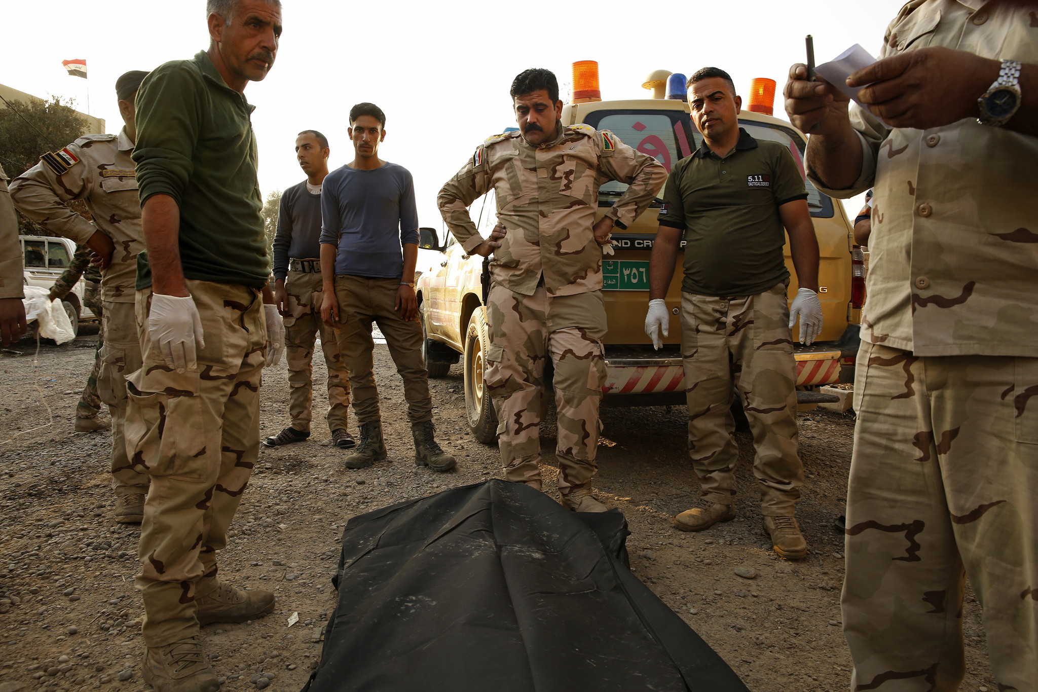 At the Iraqi Army's 9th Armored Division medical clinic, set up in a private home, doctors including Capt. Osama Fuad Rauf, center, gather around the body of a deceased soldier before he is taken to Irbil and on to Baghdad.