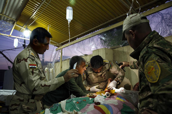 Capt. Osama Fuad Rauf works on a patient as others hold a cellphone for additional light at the Iraqi army's 9th Armored Division medical clinic.