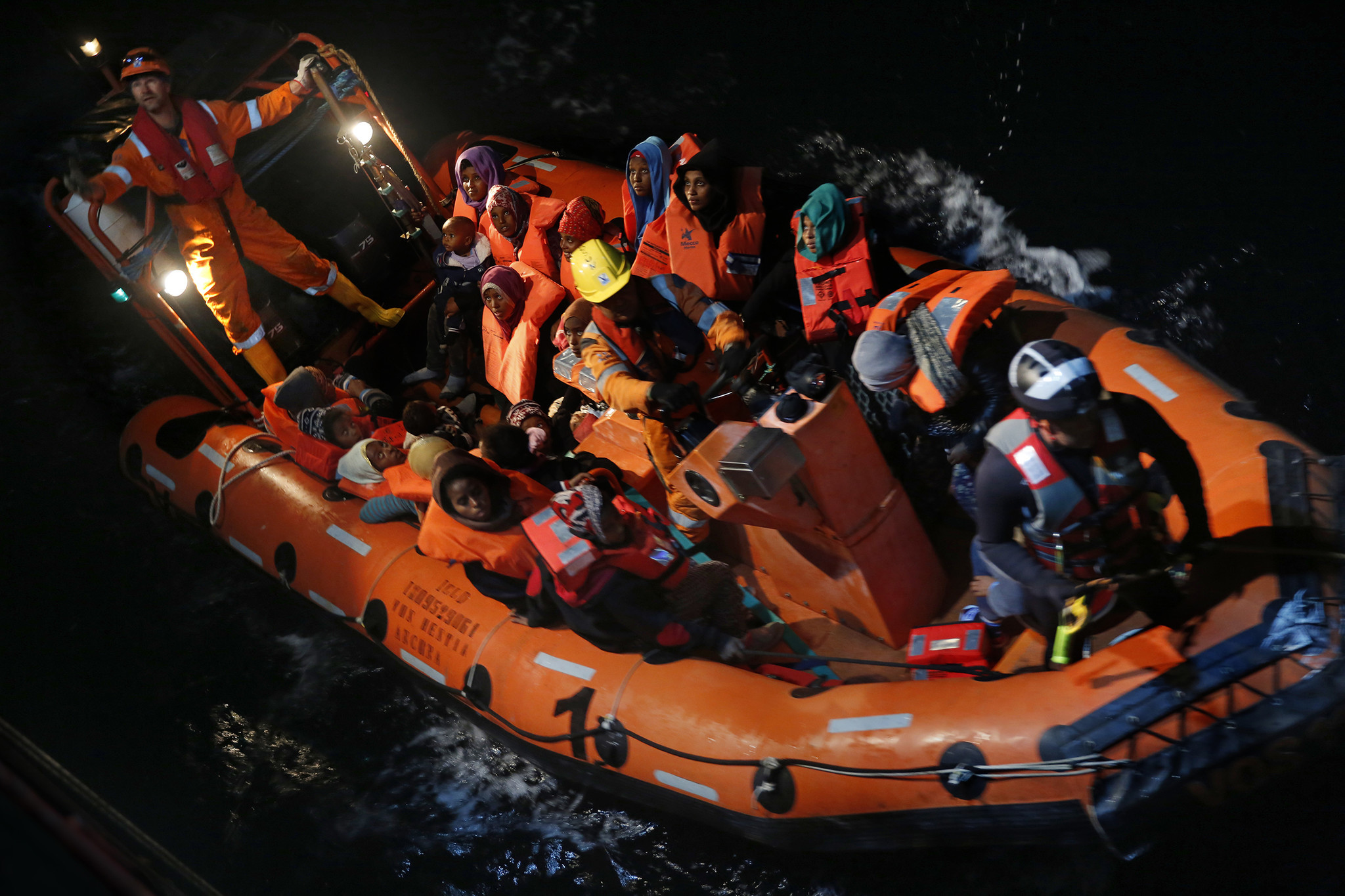 Migrants from a wooden boat are transported by the rescue team of Save the Children to the Vos Hestia off the coast of northern Libya.
