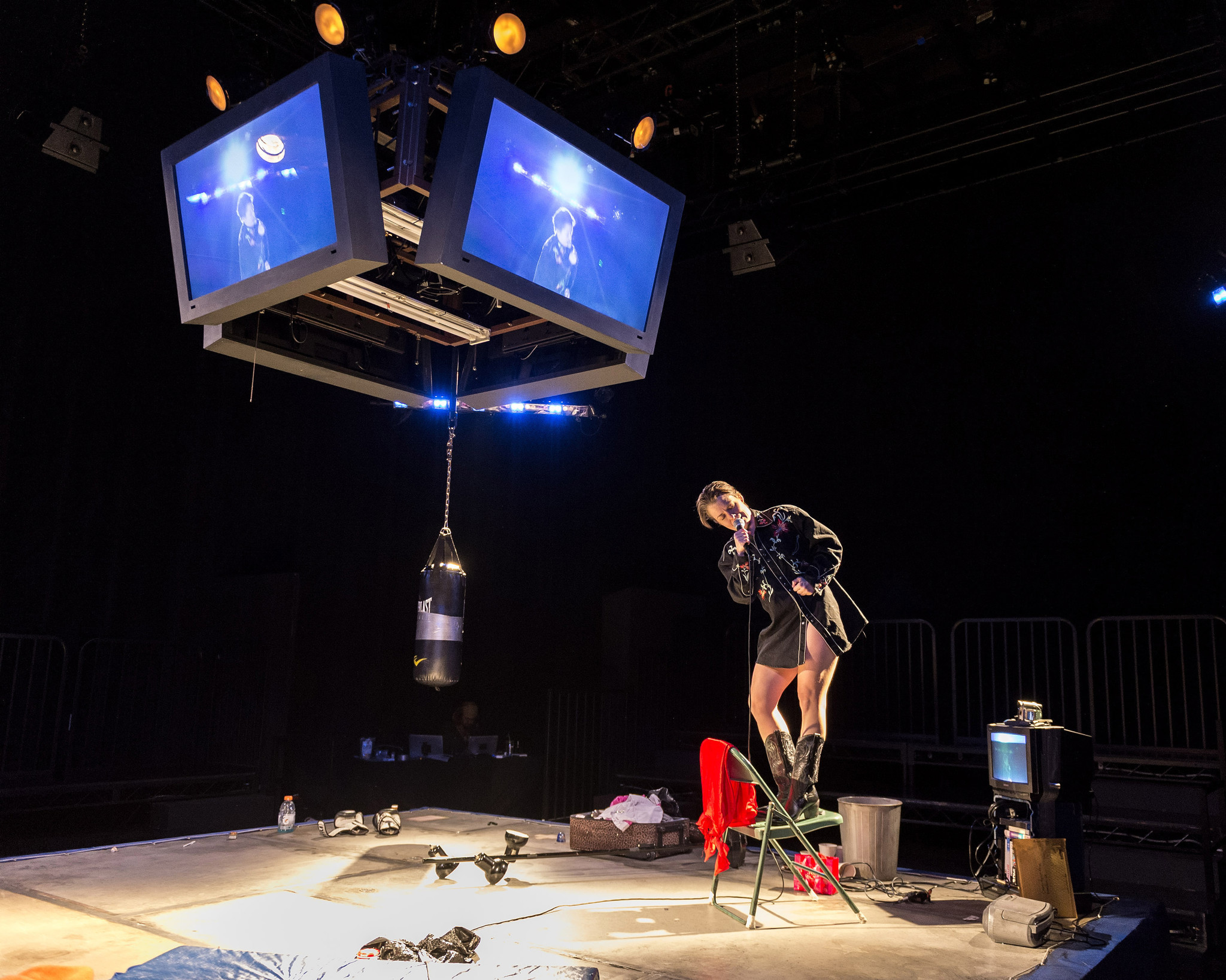 """The Wholehearted"" plays out in a boxing ring topped with monitors playing or recorded material or video shot live."
