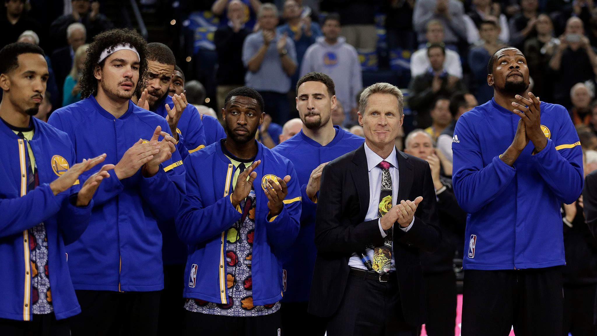 "Golden State Warriors Coach Steve Kerr, second from right, leads a ""moment of joy"" for sideline reporter Craig Sager, who died Thursday."