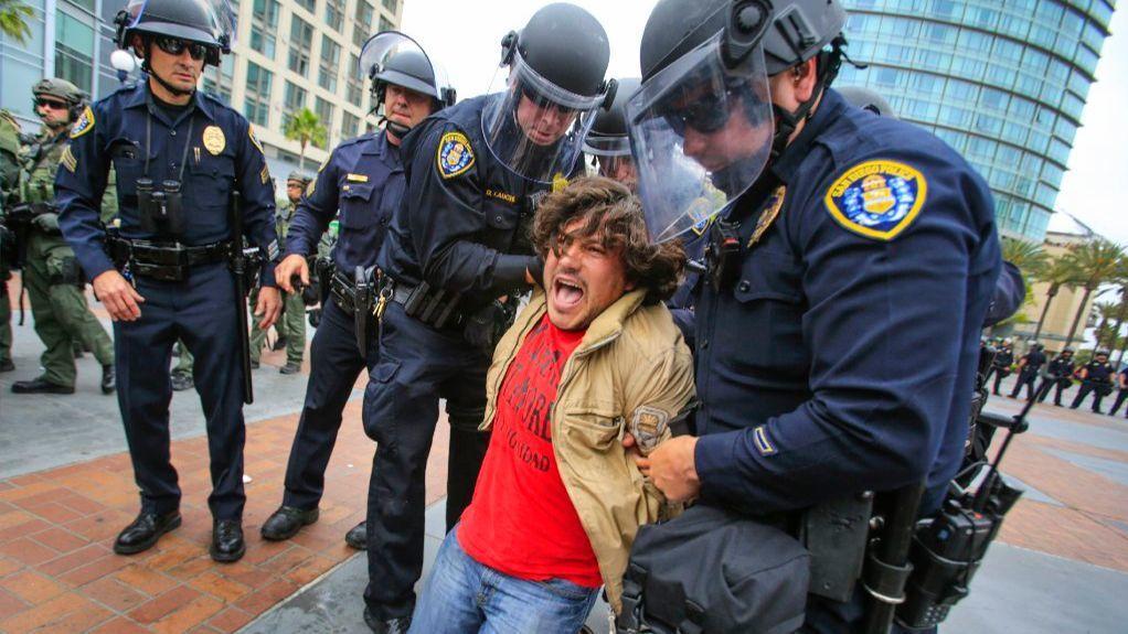 San Diego police officers in full riot gear arrest an anti Trump demonstrator near 5th Avenue and Harbor Drive in the Gaslamp Quarter after presidential candidate Donald Trump held a rally at the San Diego Convention Center.