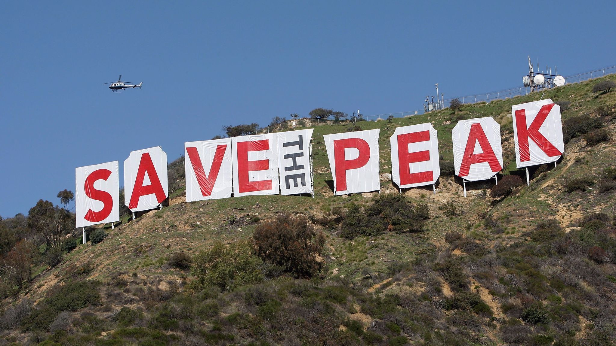 A helicopter flies over the iconic 450-foot-long Hollywood sign after activists covered it with banners during an effort to prevent the building of houses on the nearby Cahuenga Peak.