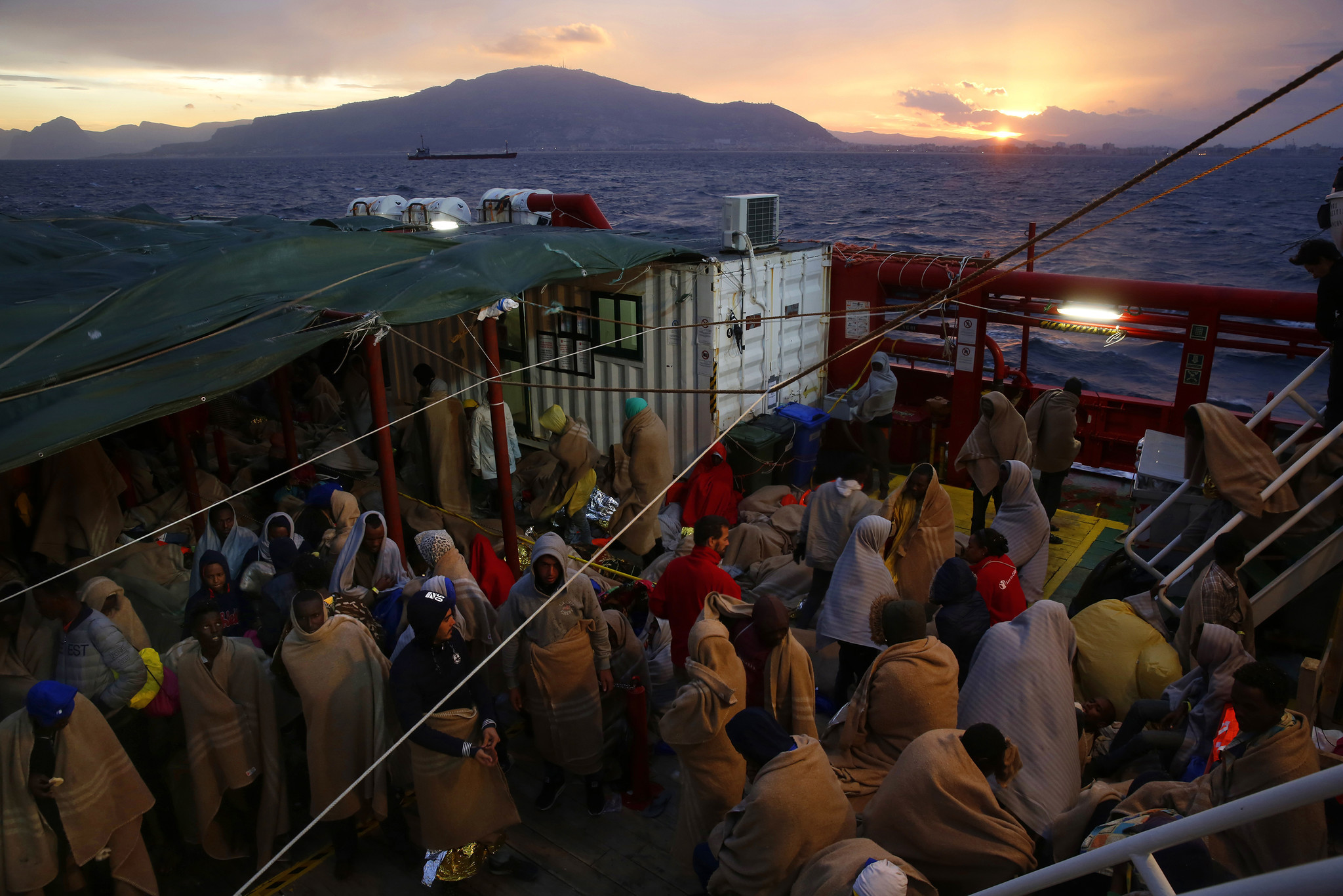 Wrapped in blankets after a night outside on deck, the rescued migrants on the Vos Hestia wait at sunrise off the coast of Sicily.