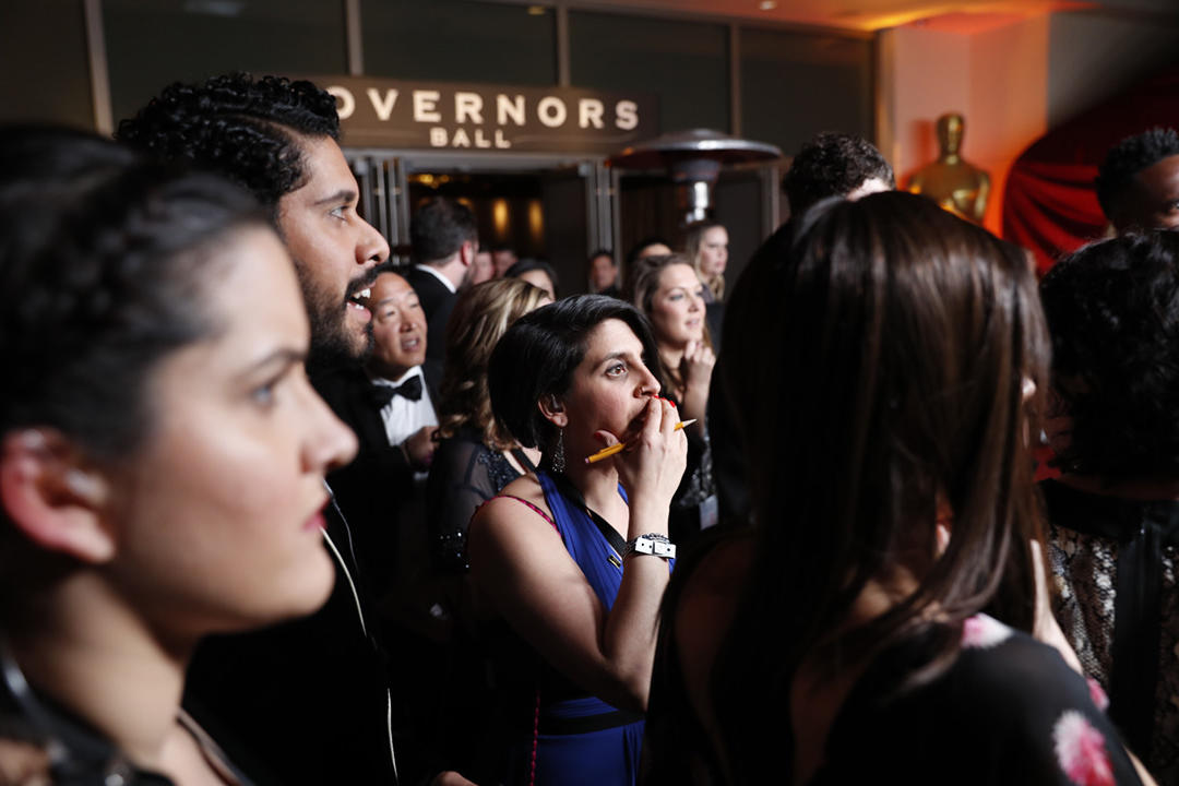 Partygoers react as the best picture mix-up is shown on monitors at the Governors Ball.