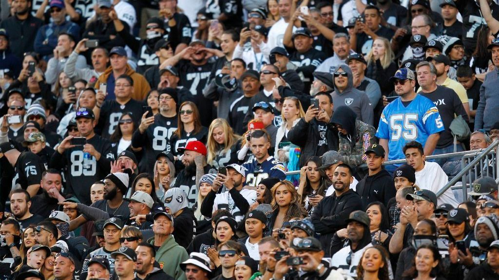 A lone San Diego Chargers fan looks on in a sea of Oakland Raiders fans at Qualcomm Stadium on Dec. 18, 2016.