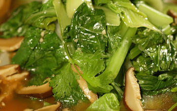 Steamed leafy greens with mushroom sauce