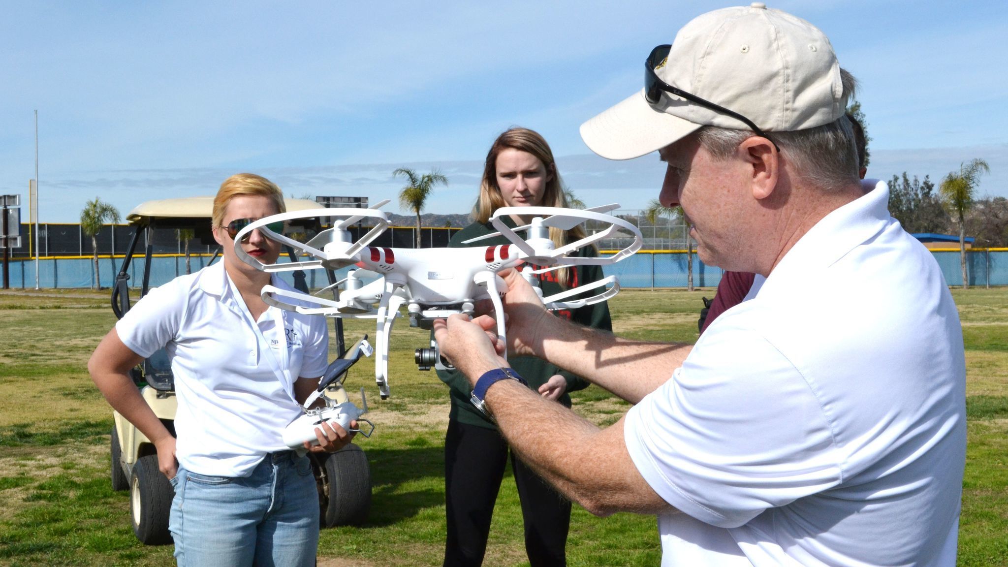NJROTC Commander Brad Davis shows features of Bulldog ONE, Ramona High's new drone, as two of his students, Alaina Sill, left, and Emma Hopperton, listen.