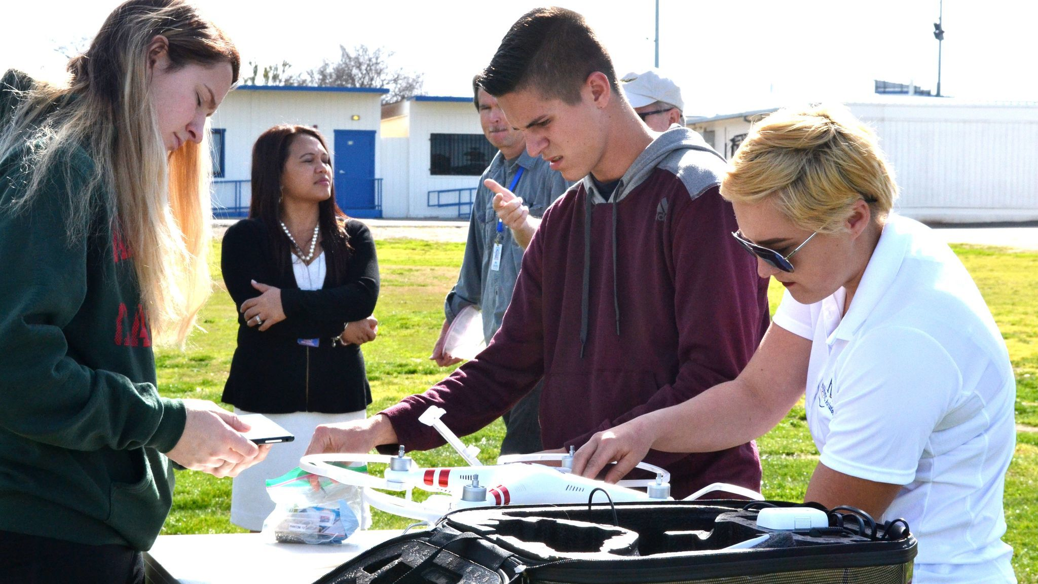 NS4 cadets Emma Hopperton, Ethan Parsons, and Alaina Sills prepare the drone for take-off.