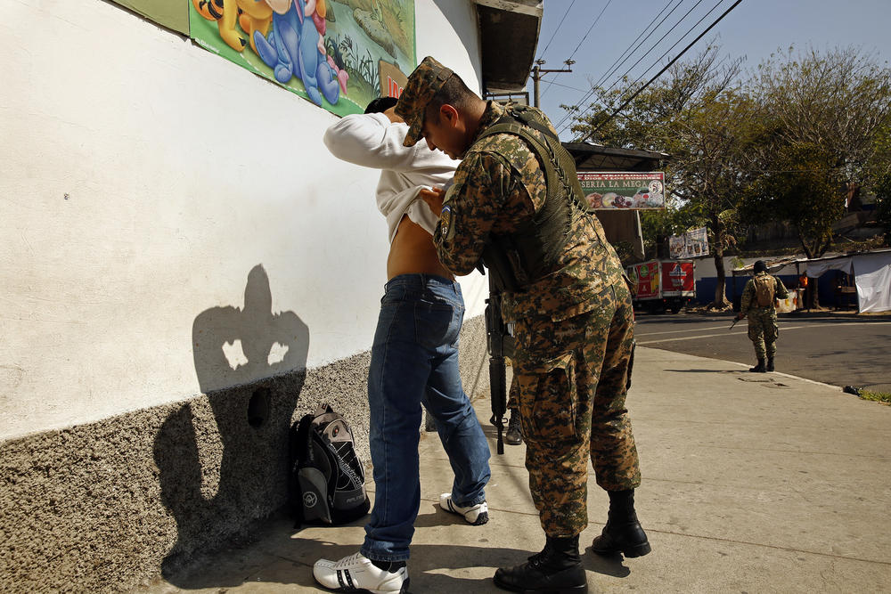 An armed soldier checks a man for gang-related tattoos. The military and police are working together to curb the gang problem, routinely stopping and frisking people.